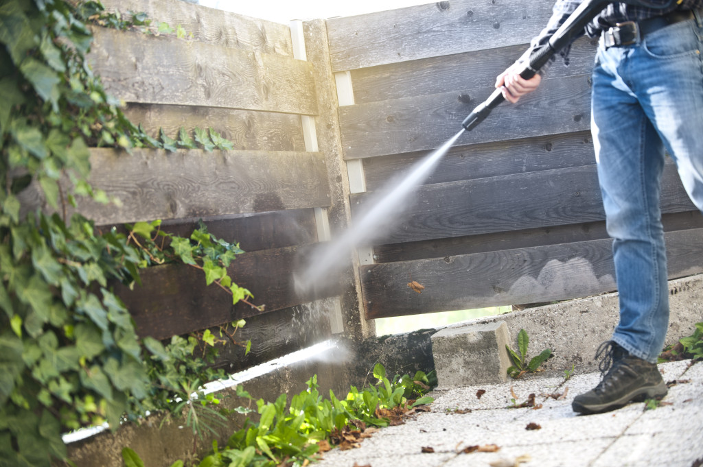 Man cleaning the back yard with high pressure washer